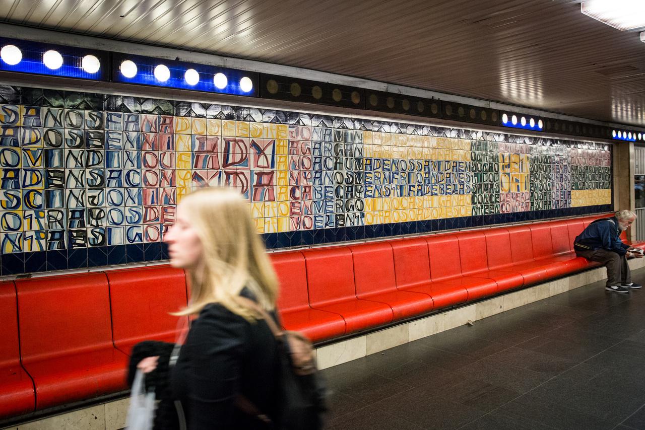Őszintén, van bárki, aki már várt a kék metrót a Deák téren, de még nem próbálta kiolvasni a portugál festőművész, Joao Vieira Csempefalának szövegét? Ha eddig nem tudtátok, mi van odaírva, elárulom: három magyar költő (Petőfi, Ady és József) versei portugálul, és három portugál költő (Camoes, Césário és Pessoa) versei magyarul. Persze ettől még olvashatatlanok hiszen csak töredékek, ráadásul – természetesen – itt is vannak rosszul felrakott csempék. Ha egy szót nem értesz belőle, akkor is jól néz ki, de azért érdekes elolvasni a fal sokszor megírt történetét például a Szerelmem, Budapest blogon.