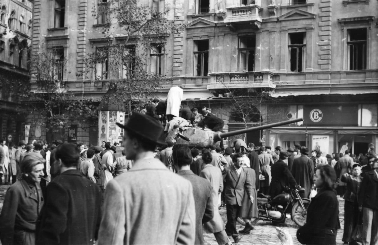 Október 23. után Pesten, elsősorban az Üllői út és a Dózsa György út környékén fotózott. Elmondása szerint ott volt az Üllői úti Örökimádás templomnál, amikor egy szovjet tank szétlőtte a templom tornyát, de ott lapult a Köztársaság tér falánál is a pártház ostromakor. Ez a fotó október 25-én vagy 26-án készülhetett: a 070-es jelzésű, harcképtelenné tett T-34-es szovjet harckocsi a Krúdy Gyula utcánál napokig állt a József körúton, ezért jól ismert a forradalmi képekről.