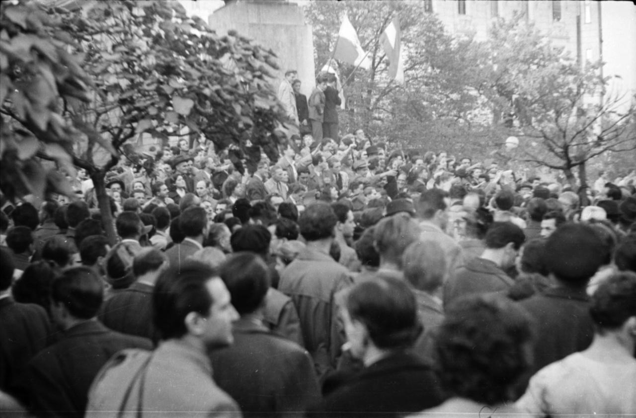 """Október 23-án a Zrínyi Akadémia diákjai Márton András ezredes vezetésével csatlakoztak az egyetemisták követeléseihez, és úgy döntöttek, a """"petőfisekkel"""" együtt ők is részt vesznek a délutáni felvonuláson. Faragó György is az akadémia tagjaival indult el: katonai teherautókkal mentek a Margit-hídig, onnan gyalog tovább a Bem tér felé. Bár a tüntetés kezdetét az utókor a műegyetemistákhoz köti, a fotókon is látszik, hogy mire az egyetemista csoportok megérkeztek, a tér már majdnem tele volt. A képen magyar és lengyel zászlók a Bem-szobor talapzatán."""