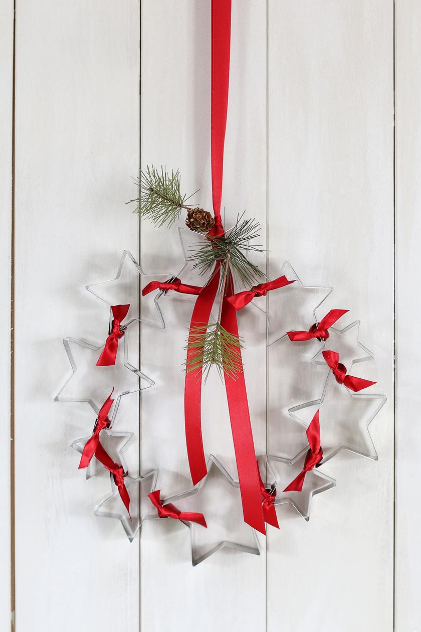Ehhez az ajtódíszhez például csak néhány csillag formájú süteményszaggató kell, illetve egy piros szalag.