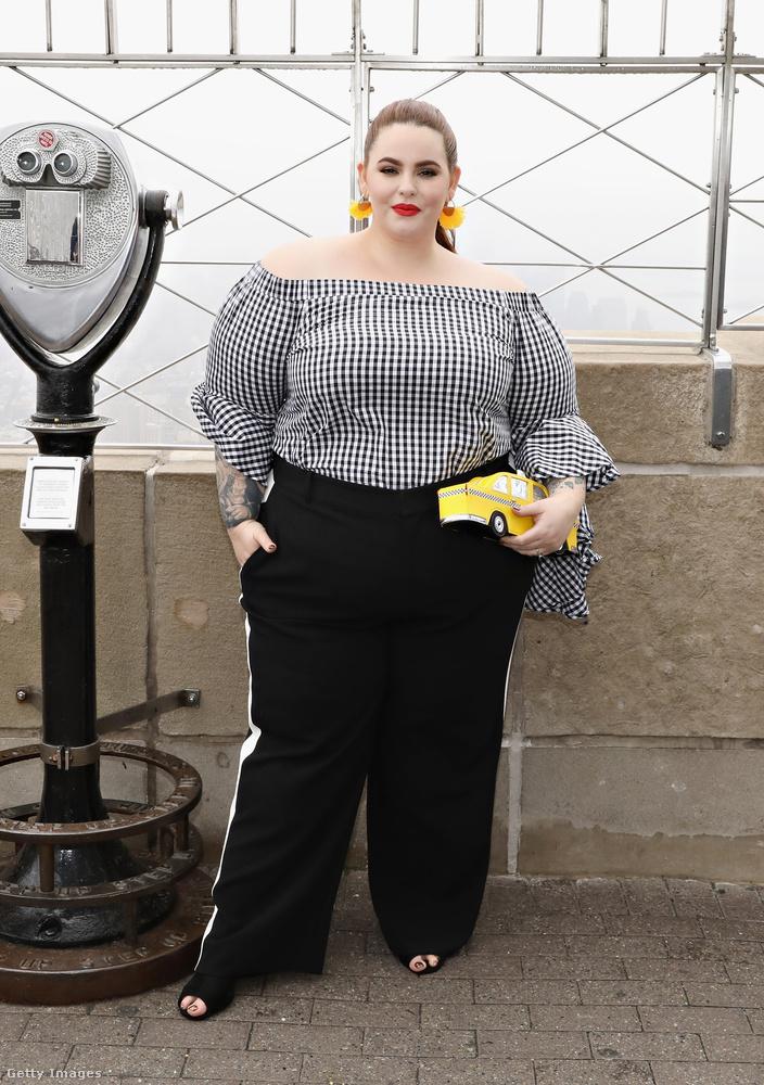 Vállvillantós blúz, oldalt csíkos tréning nadrág és sárga taxi formájú kistáska Tess Holiday-en.