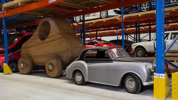 Két furcsaság egy képen: hatalmas fakocsi, még Flintstone Frédi is megirigyelné, mellette pedig egy zsugorított, vélhetően egy kisebb Peugeot-ra épített Rolls-Royce