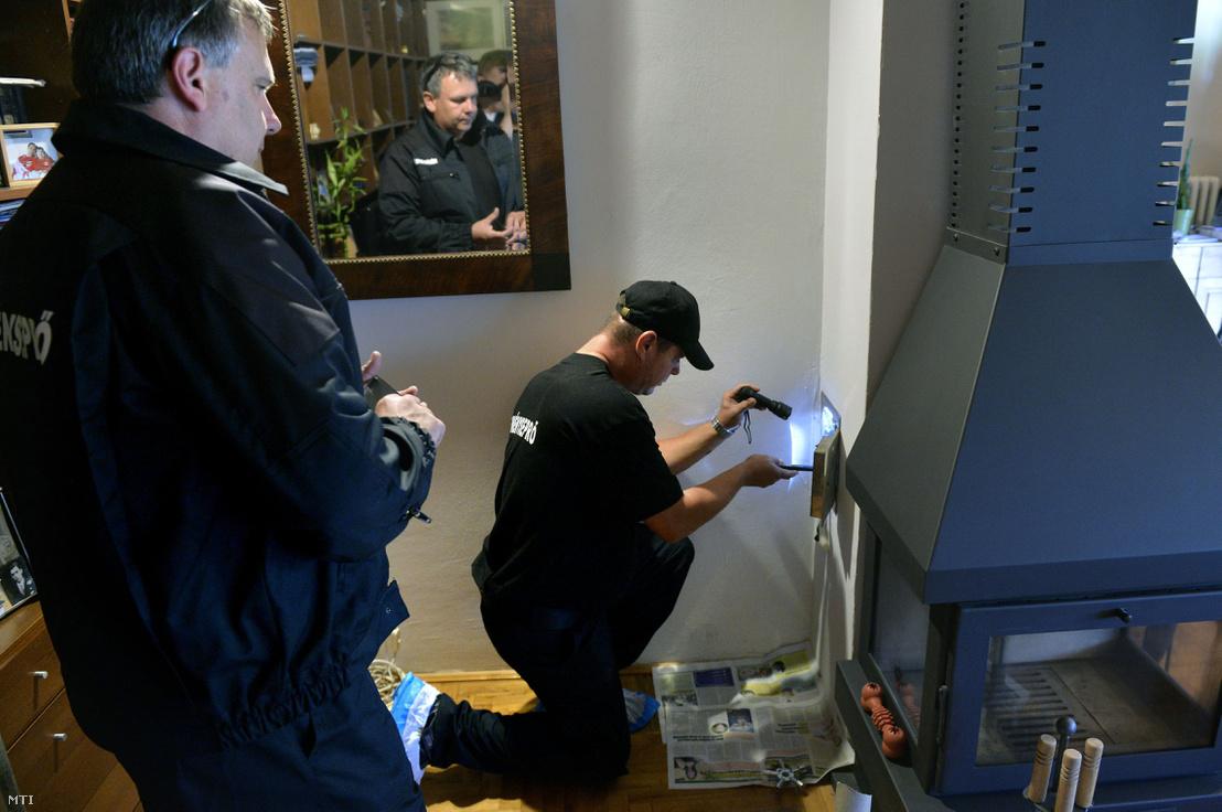 A katasztrófavédelem kéményseprőipari szakembere egy kandalló kéményét ellenőrzi tükörrel egy csobánkai családi házban 2016 július 18-án