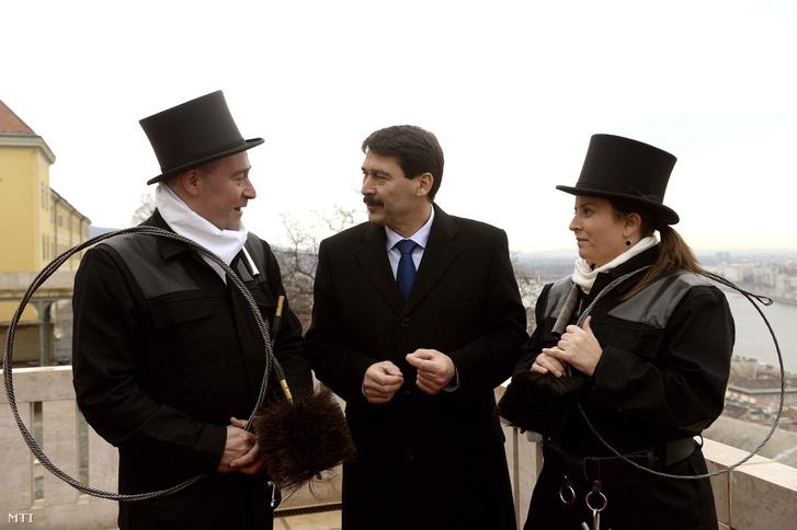 Áder János beszélget a Fővárosi Kéményseprőipari Kft. két kéményseprő mesterével a Sándor-palota teraszán 2015. január 9-én, a köztársasági elnök és a kéményseprős szokásos újévi köszöntésén.