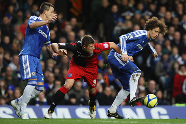 David Luiz (R) and John Terry of Chelsea (L) foil Marko Futacs of Portsmouth during the FA Cup sponsored by Budweiser Third Round match between Chelsea and Portsmouth at Stamford Bridge on January 8 2012 in London England.