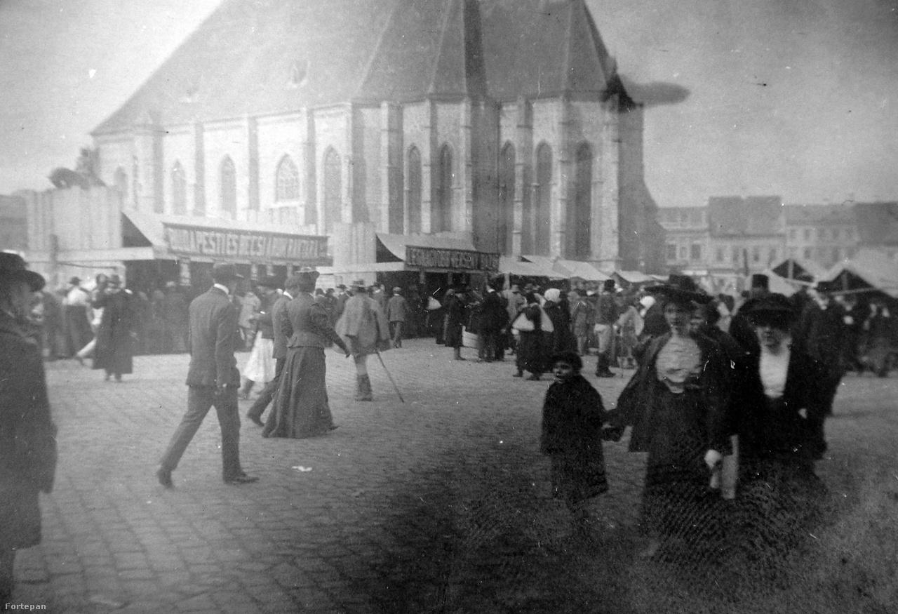 """A kép 1902 után készülhetett, mert a Mátyás szoborcsoport már a helyén, és a templom körüli épületeket is lebontották. A """"budapesti és bécsi áruk raktárának"""" nevezett ideiglenes fabódé körüli tolongás és a vásári hangulat megörökítése annyira érdekelte a fotóst, hogy a Szent Mihály tornyát elfelejtette belekomponálni a képbe. A szemmel végigmérhető külsők spektruma tágas: van itt úri viselet, népviselet, női kalapviselet. A kiáltozó kisgyerek figurája különösen életszerűre sikeredett, míg szülei elmosódó árnyak maradnak."""