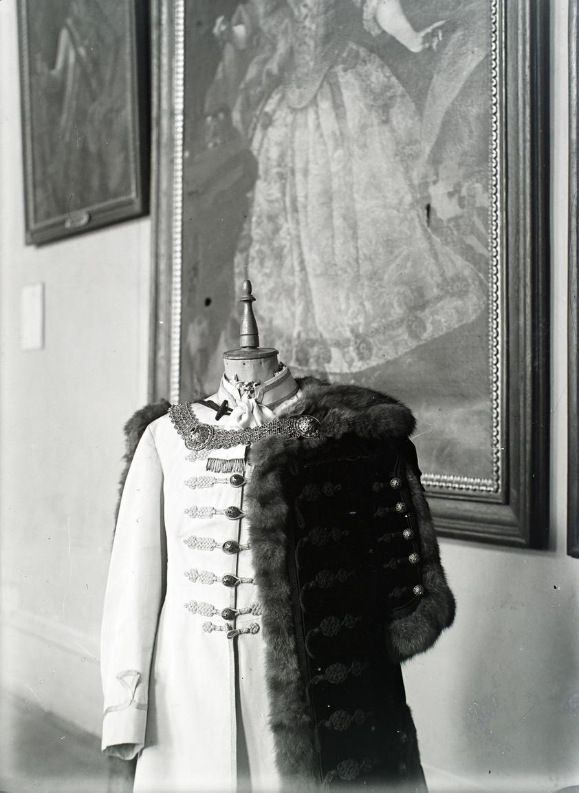 """A próbababán férfi díszmagyar, háttérben a borsodi vármegyeháza díszterme Miskolcon. Megrendelői ebben az időszakban már bizonyára rendesen fizettek, de az 1920-as évek végére, 1930-as évek elejére visszautalva Bánovszky megjegyezte, hogy """"nehéz időszak volt, mert a magas állású emberek is csak részletekben tudtak fizetni""""."""