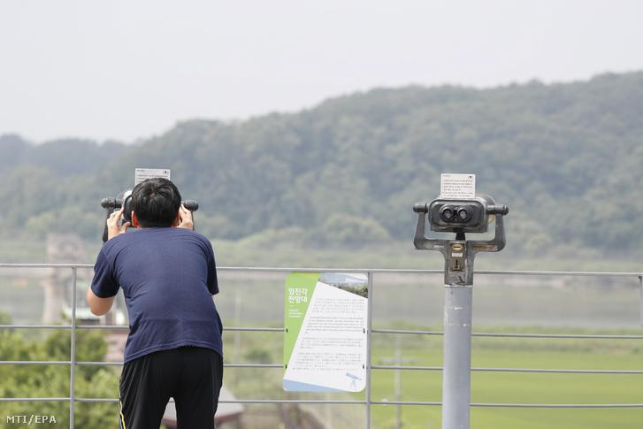Egy férfi távcsõvel néz át Észak-Korea területére a dél-koreai oldalról a két Koreát elválasztó panmindzsoni demilitarizált övezetben fekvõ Padzsu közelében