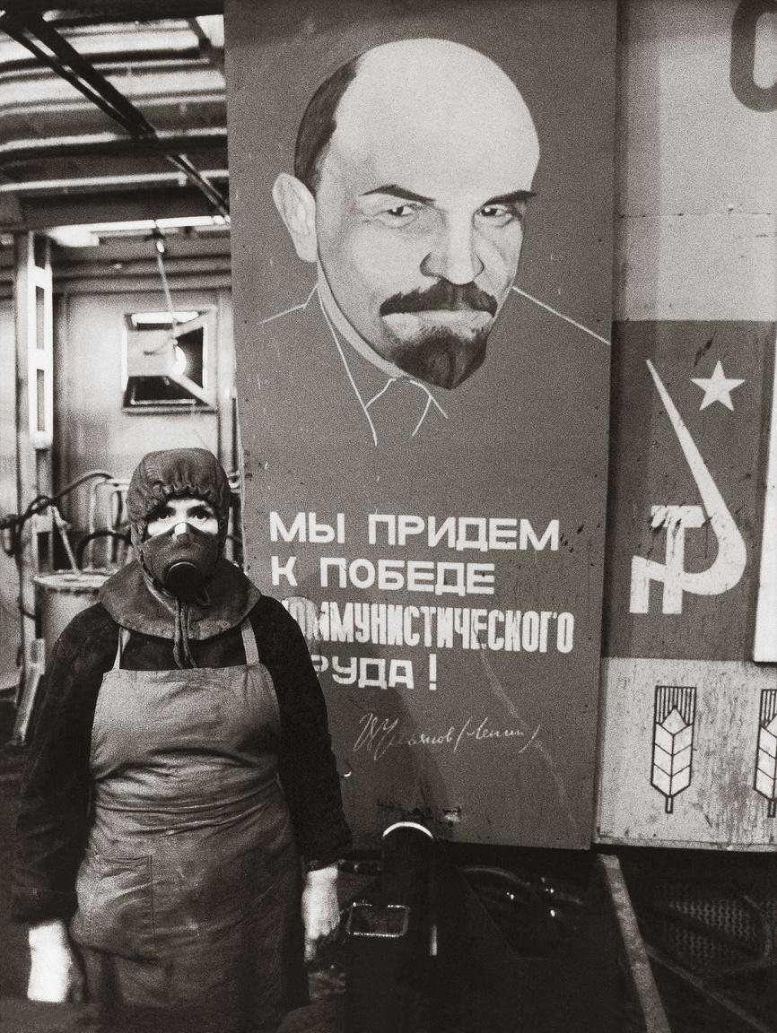Kazakhsztán, Karaganda, 1988. Gyári munkás a kommunizmus győzelmét hirdető üzemi plakát előtt.