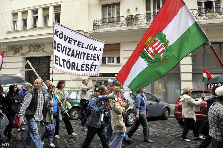 Tüntetõk vonulnak egy Követeljük a devizahitelek eltörlését feliratú transzparenssel a Kúria épületétõl a Képviselõi Irodaházhoz 2013. június 25-én.