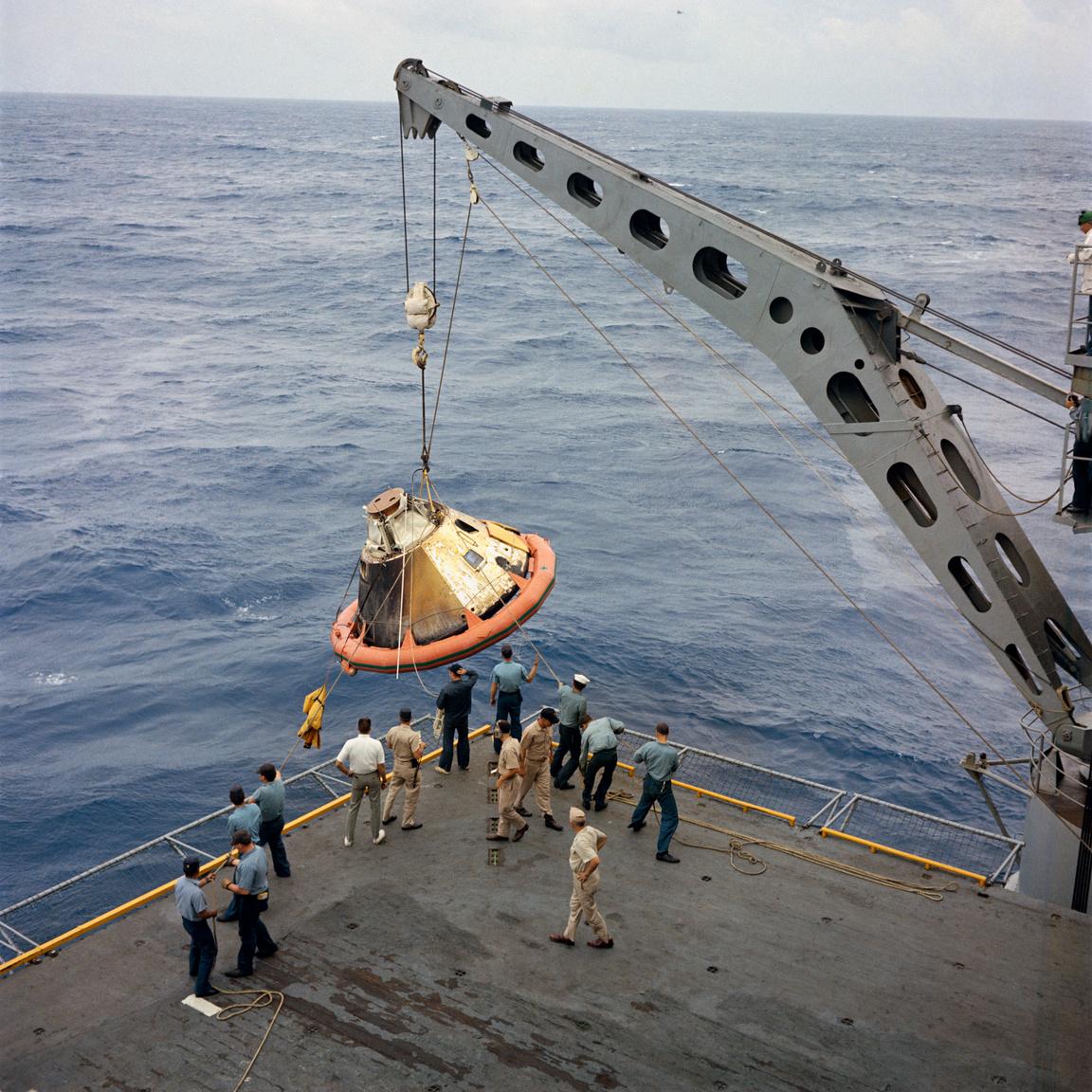 """Az amerikai  haditengerészet USS Bennington repülőgéphordozójának fedélzetére emelik a Csendes-óceánba, Honolulutól 1730 kilométerre északnyugatra vízbe csapódó űrhajót. A CSM 017-et a dereka körül látható narancssárga """"úszógumi"""" tartotta a víz felszínén."""