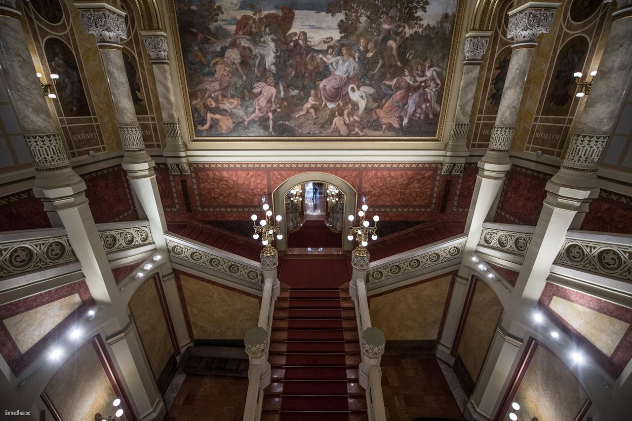 Az urak és hölgyek pedig felsétálhattak a pompás lépcsőn, Lotz Károly hatalmas képe alatt. Ez volt az első, nem egyházi megrendelésre készült falfestmény, amely középületet díszített Pesten. A témánál kikötés volt, hogy magyar regét kell választani, de az alkotó szeretett volna valami könnyedet és egyetemeset. Így esett a választás az Árgírus királyfi és Tündér Ilona mesére, mely más népeknél is megtalálható, s ezért néznek ki úgy a szereplők, mintha a görög mitológiából léptek volna elő.