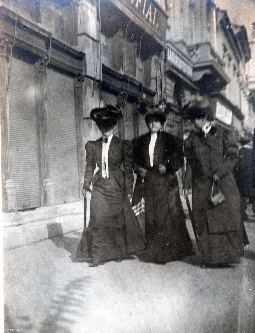 A női séta elmaradhatatlan kellékei: az elegáns kalap és az ernyő. A bolfeliratokat nem lehet kibetűzni, az épületek homlokzatából kiindulva a Mátyás tér északi oldalán lehetünk.