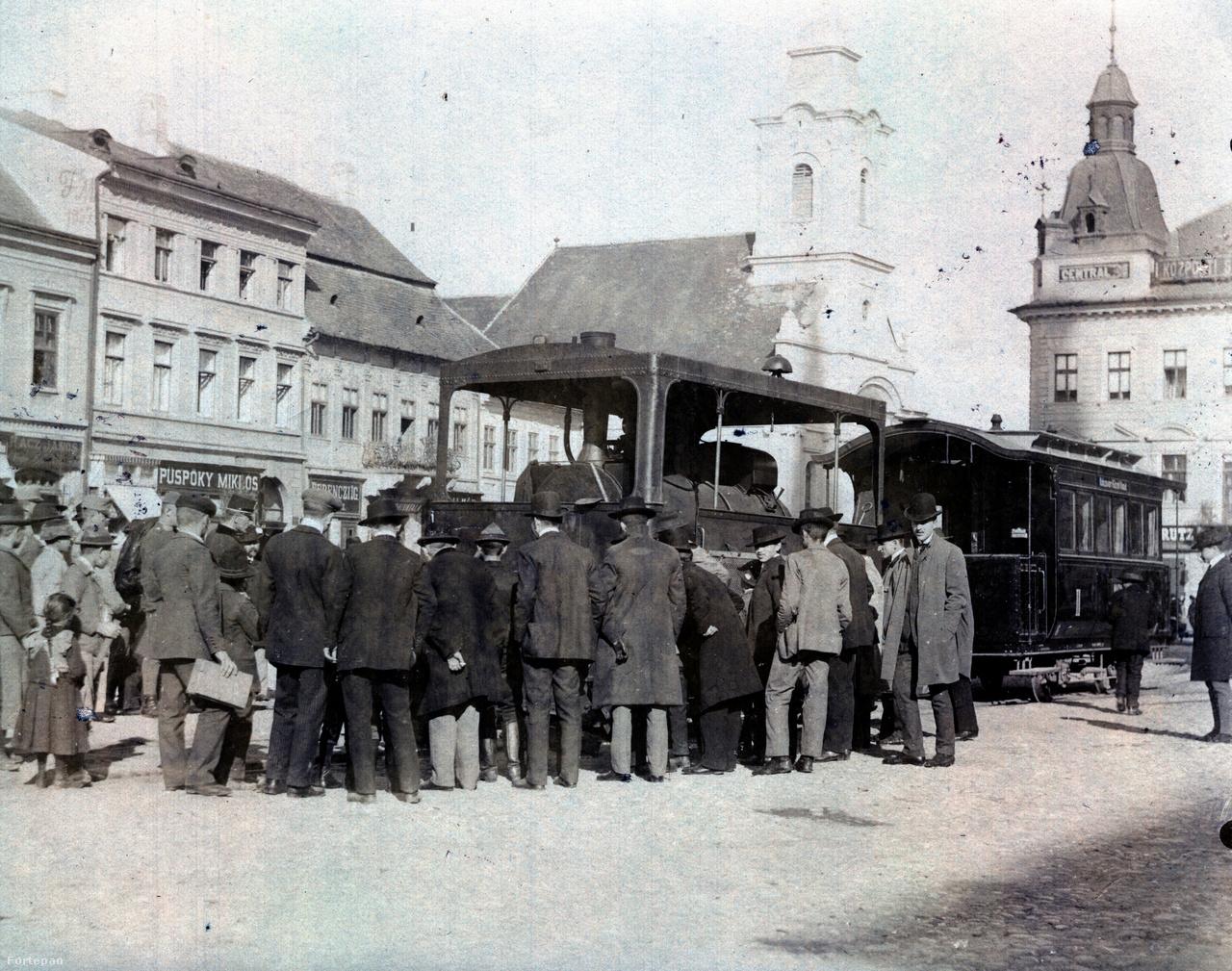 """Ezen a fotón egy kisebb tömeg mutat hátat a fényképezőgépnek. Vajon milyen szenzáció köti le ennyire a figyelmüket? És vajon miért nem ment a fotós még közelebb a látnivalóhoz? Nem tudhatjuk. A mai nézőnek mégis feltárulkozik egy másik egzotikum: a gőzhajtással működő kisvasút, amely 1893-tól az állomást kötötte össze a Monostorral és Kolozsvár külvárosával, a Hóstáttal. Az """"ájvájnak"""" csúfolt városi vasút számos balesetet okozott, és úgy gondolták, hogy rontja a központ arculatát is, mert a sínek és a megállók állomási hangulatot keltettek a belvárosban. 1902-ben felszámolták, utolsó kolozsvári útján a Mátyás szoborcsoport darabjait szállította az állomásról a főtérre. A szerelvényeket később Debrecenbe vitték, hogy ott fuvarozza a városi sétálókat."""