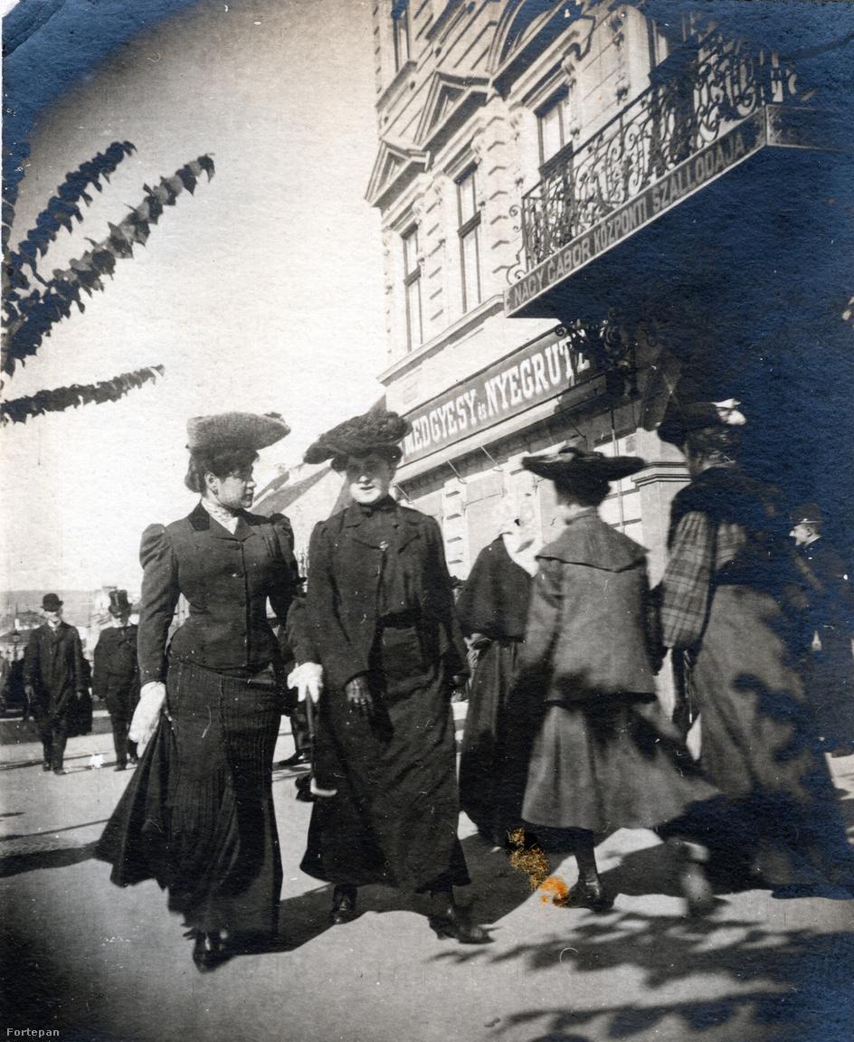 Street-fotó a fűzött derekak korszakából, amelyen az összeöltözött kalapos hölgyeket a kesztyűk színe különbözteti meg egymástól. A fotós annyira követte a lencsevégre kapott korzózók mozdulatait, hogy velük együtt enyhén dőlt a kép is. A fotó a fő tér sarkán, a mai Melody Hotel előtt készült.