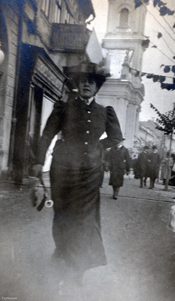 Ugyanazon az utcán, pár lépésnyivel odébb: egy hölgy, szigorúan hátratett kézzel. A háttérben az evangélikus-lutheránus templom látszik.  A tőle jobbra álló épületben nyílt meg a Párizs Mozi 1907-ben, ezért a hölgy feje fölötti tábla akár mozireklám is lehetne. Sőt az egész kép olyan, mintha mozogna, mintha egy filmkocka volna.