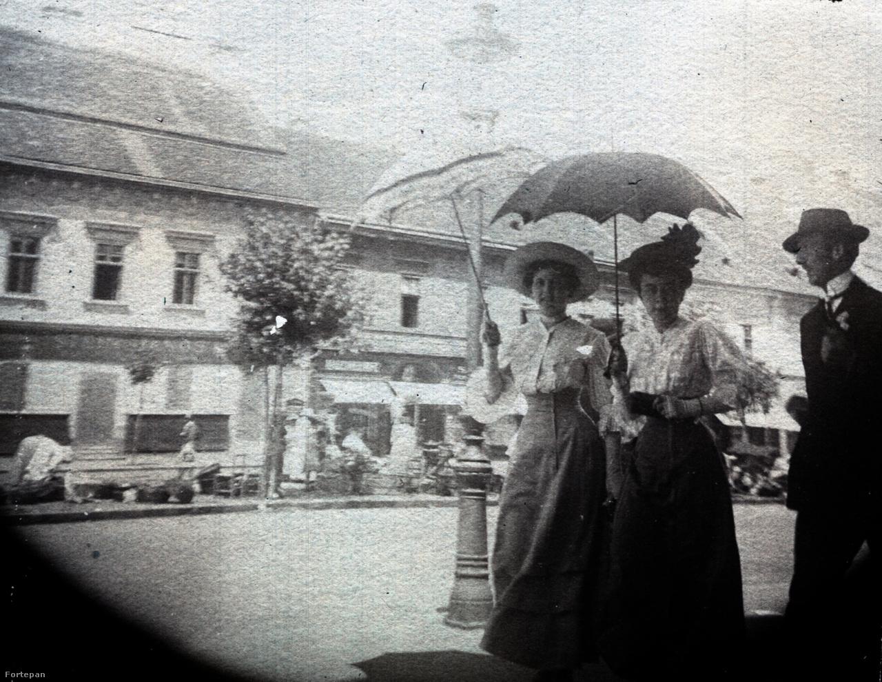 """Leszármazottaik azonosították a képbe besétáló napernyős csapatot. Eszerint Krajnai Hudolin Emmát, mellette Törös Marcsát, a kolozsvári opera szopránját láthatjuk férjével, Krajnai Hudolin Lajos, ügyvéddel. A járda szélén vásározó emberek és a bezárt bolt ajtók alapján vasárnap lehetett. A bolt cégérén Stein János nevét betűzhetjük ki, aki a 19. században Kolozsvár legmenőbb papír- és könyvkereskedését vezette, mely mellékesen könyvkölcsönzéssel is foglalkozott. Gyulai Pál szerint a könyvesbolt a város """"szellemi kocsmája"""" volt."""