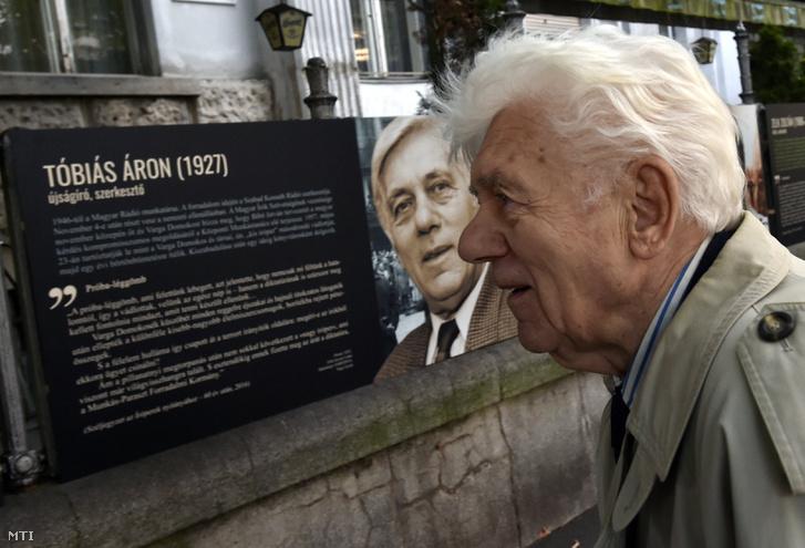 Tóbiás Áron újságíró, szerkesztő az őt ábrázoló fénykép előtt az Írók a forradalomban - 1956 című kültéri kiállítás megnyitóján a Magyar Írószövetség épületénél 2016. október 5-én.