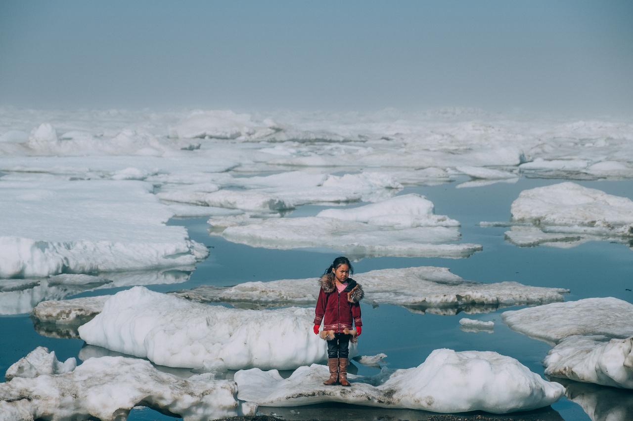 Egy iñupiat lány áll egy jégtáblán Alaszka partjainál. A mérések szerint az Arktisz felmelegedésére utaló hosszú távú trendek romlanak, és a nyár végeztével sem javulnak, amikor az Északi-sarkvidéken rendszerint hízni szokott a hó és a jég. Ezek a változások viszont kihatnak az állatvilágra, ezen keresztül pedig az itt élő emberek életét is befolyásolja.