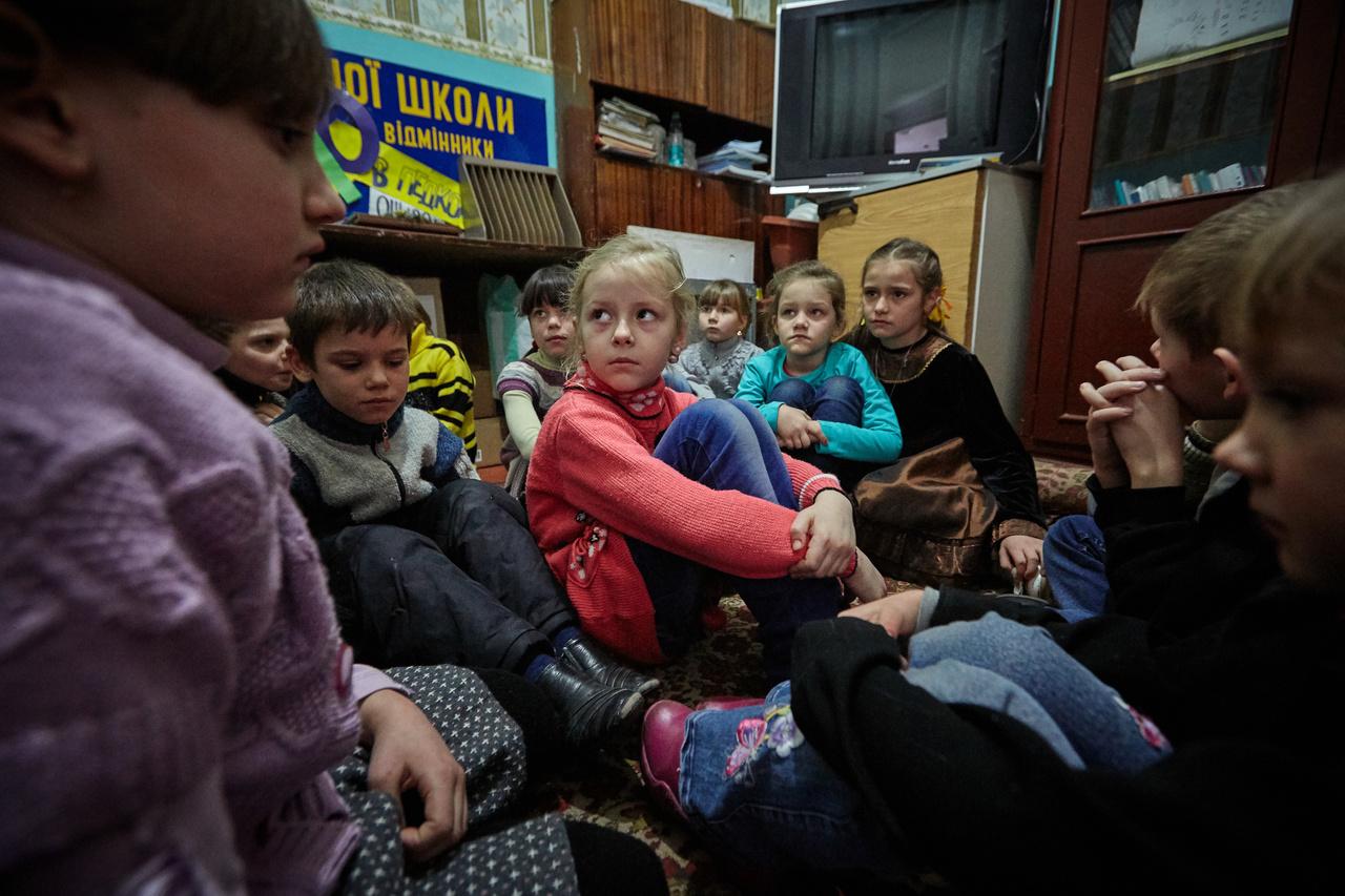 Alsósok gyakorolják Kelet-Ukrajnában, hogyan kell reagálniuk tüzérségi támadás esetén. A Kelet-Ukrajnában negyedik évébe lépő konfliktusban továbbra is aktív harcok vannak, a különböző tűzszüneteket pedig rendre megszegik. A harcok miatt 1,7 millió embernek kellett elhagynia az otthonát. A leginkább azok a családok vannak nehéz helyzetben akik még mindig a frontvonal 15 km-es körzetében laknak. Ezen a részen 200 ezer gyerek él, közülük 12 ezren olyan településen laknak, amit legalább havonta egyszer ér tüzérségi támadás.