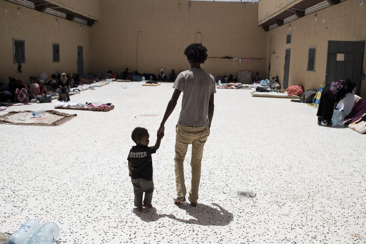 Egy eritreai férfi a 30 hónapos fiával az egyik líbiai táborban, ahova leginkább olyan illegális migránsok kerültek, akik megpróbáltak a Földközi-tengeren keresztül Európába jutni. A legális státusz nélküli külföldieket akár 12 hónapig bent tarthatják. A körülmények siralmasak, van, ahol több mint 50 ember zsúfolódik 25 férőhelyre. Az eritreai férfi a gyerekük születése után indult el otthonról előbb Szudánba, majd Tripoliba. Felesége út közben meghalt, őt a kisgyerekkel pedig még Tripoli előtt elfogták.