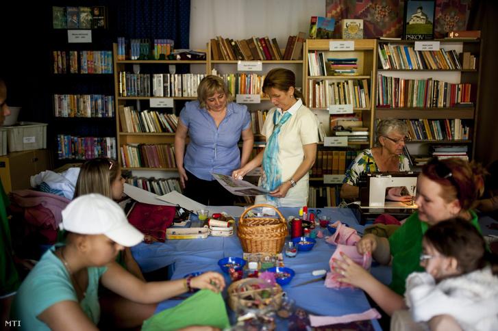 Herczegh Anita, Áder János köztársasági elnök felesége (középen j), Gyura Barbara, a Szemem Fénye Alapítvány elnöke (középen b) társaságában egy képet néz a Gyermekhospice Hősei Hét megnyitóján a pécsi Dóri Házban 2014. június 13-án