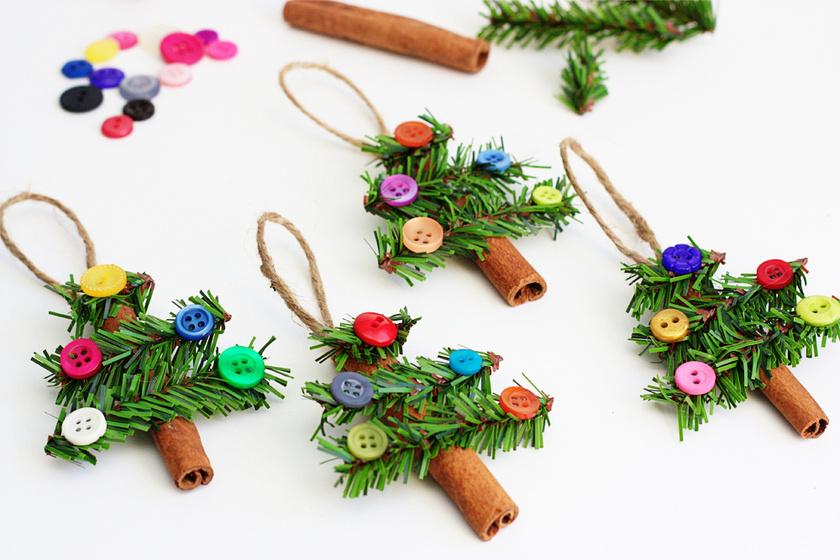 Pillanatragasztóval ráerősítheted a fahéjra a miniatűr fenyőágakat és a gombokat. Ezután már csak az akasztóját kell felragasztanod, és ezzel el is készült a tökéletes karácsonyfadísz!