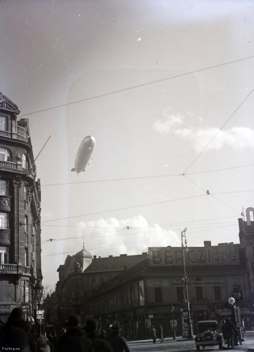 A Kálvin téren keménykalapos bámészkodók nézik a Ráday utca fölött elúszó Zeppelint. Balra a Gazdák Biztosító Szövetkezetének székháza, jobbra egy Rex benzinkút, mögötte a Budapest Székesfőváros Felsőbb Zeneiskola.