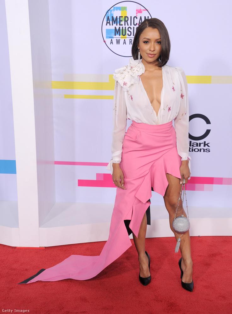 A svájci születésű amerikai színésznő, Kat Graham a Ronald van der Kemp mélyen dekoltált blúzát és féloldalas pink szoknyáját viselte az AMA-n.