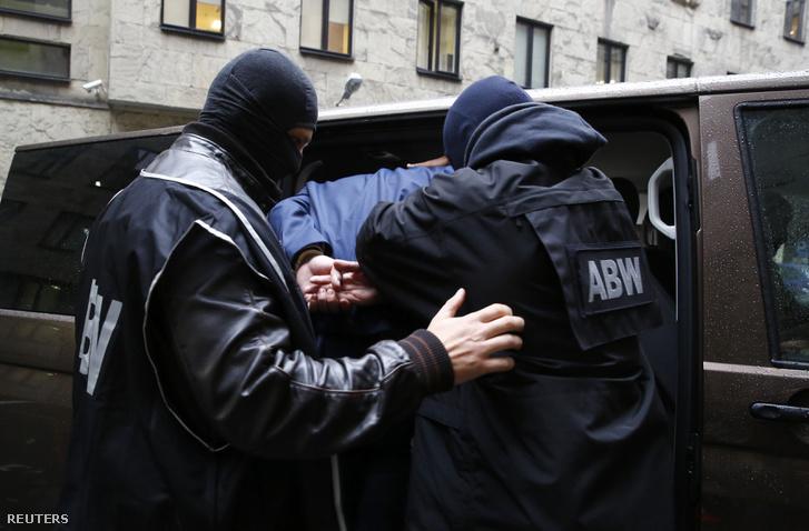 A Lengyel Belföldi Biztonsági Ügynökség (ABW) emberei egy orosz kémkedéssel gyanúsított férfit ültetnek be egy furgonba 2014. október 17-én