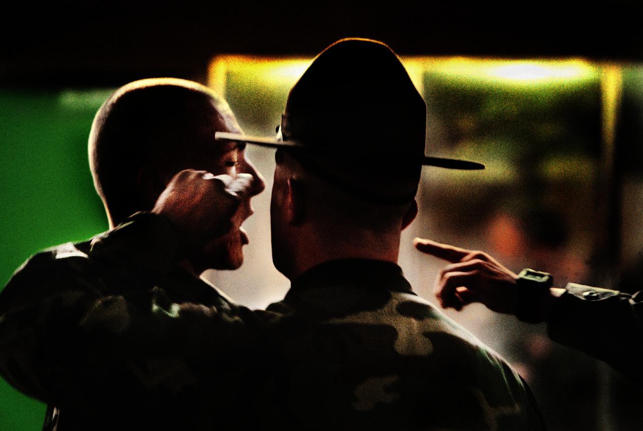 """A főtörzsőrmester éppen kiosztja az egyik újoncot. A Parris Island-i kiképzőtábor a kemény elvárásokkal és kimerítő fizikai kiképzéssel a legdurvább a fegyveres erők kiképzési központjai közül. A kiképzés egyik alapelve, hogy feszegetnie kell a határokat, de több esetben már konkrét visszaélések derültek ki, és Parris Islanden a többi katonai kiképző támaszponthoz képest sokkal messzebb mentek a kiképző őrmesterek az újoncok vegzálásában. """"Valóban ez az egyetlen módja, hogy harcost képezzünk?"""" - tette fel a kérdést részletes cikkében a New York Times."""