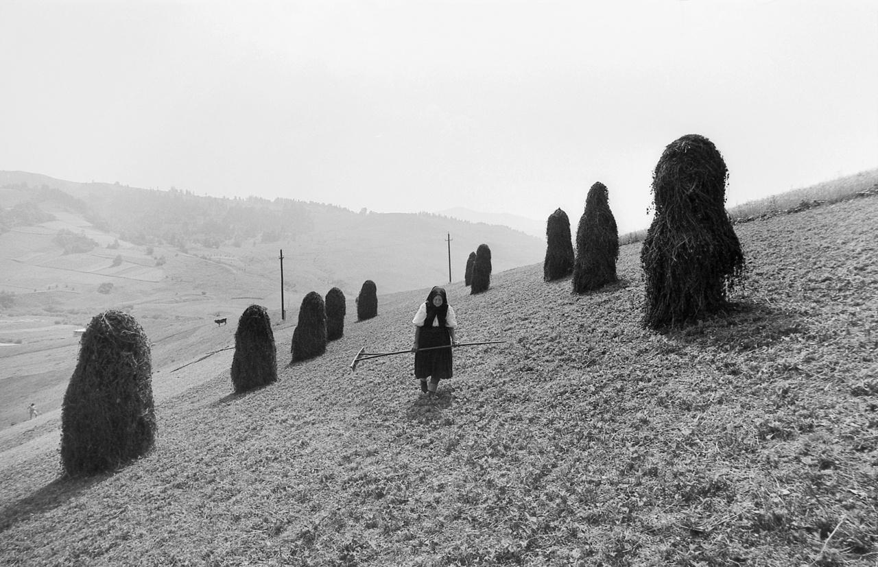 Korniss Péter első képei Erdélyben, valamint Magyarországon és a környező országokban készültek. Olyan falvakban, amelyek a szocialista viszonyok között is megőrizték a paraszti kultúrát. Ez egy asszony a kazlak közt, 1976-ban.