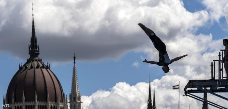 17. vizes világbajnokság óriás-toronyugrásának egyik versenyzője edz a Batthyány térnél 2017. július 26-án. A háttérben az Országház kupolája.
