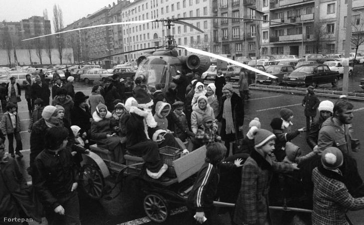 Lehet, hogy az amerikai Télapó rénszarvas szánon száll, de a magyarnak van helikoptere és pónifogata. A gyerekeket mondjuk az utóbbi jobban le is köti, mint a csoki. 1976-ban a XI. kerület megadta a módját az ünneplésnek. (Október huszonharmadika (Schönherz Zoltán) utca, a Skála Budapest Szövetkezeti Nagyáruház parkolója, szemben a Bercsényi utca házsora.)