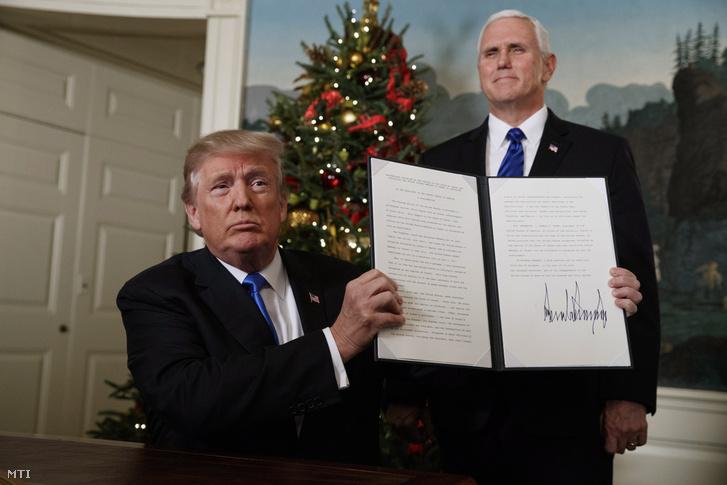 Donald Trump amerikai elnök mutatja az általa aláírt Jeruzsálemet Izrael fővárosaként elismerő dekrétumot Mike Pence alelnök jelenlétében a washingtoni Fehér Házban 2017. december 6-án.