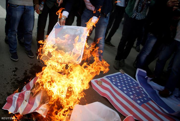 Palesztin tüntetők amerikai zászlókat és Donald Trump amerikai elnök portréját égetik a döntést követően Gázavárosban