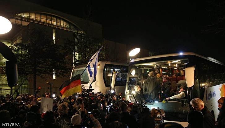 Menekülteket szállító busz érkezik a berlini kancellária épületéhez 2016. január 14-én. Peter Dreier a bajorországi landshuti járás elöljárója a szövetségi kormány menekültpolitikája elleni tiltakozás jeleként egy busznyi menekültet szállíttatott a kancellária épülete elé.
