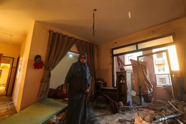 Palesztin nő tér vissza lakásába, amit légitámadás ért a Gázai övezetben lévő Bét Lahia településen.A rakétatámadások azután kezdődtek, hogy Donald Trump amerikai elnök szerdán bejelentette:  az Egyesült Államok Izraelben lévő nagykövetségét Tel-Avivból áthelyezik Jeruzsálembe, amelyet Izrael fővárosaként ismer el.