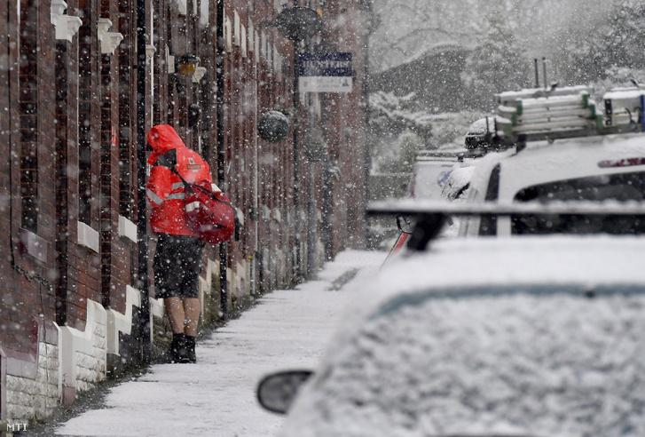 Rövidnadrágot viselő postás kézbesít egy levelet a szakadó hóesésben a Manchester közelében fekvő Stalybridge-ben 2017. december 9-én.