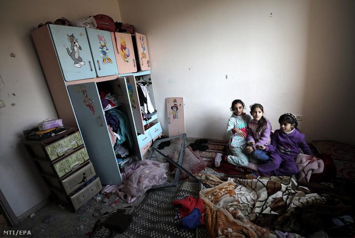 Palesztin gyerekek az izraeli légicsapásban megrongálódott otthonukban a ciszjordániai Beét-Lahijában
