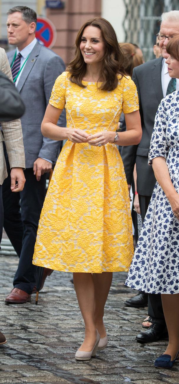 Rövidujjas, térdig érő sárga Jenny Packham ruha és bézs háncstalpú cipő Heidelberg történelmi negyedében.