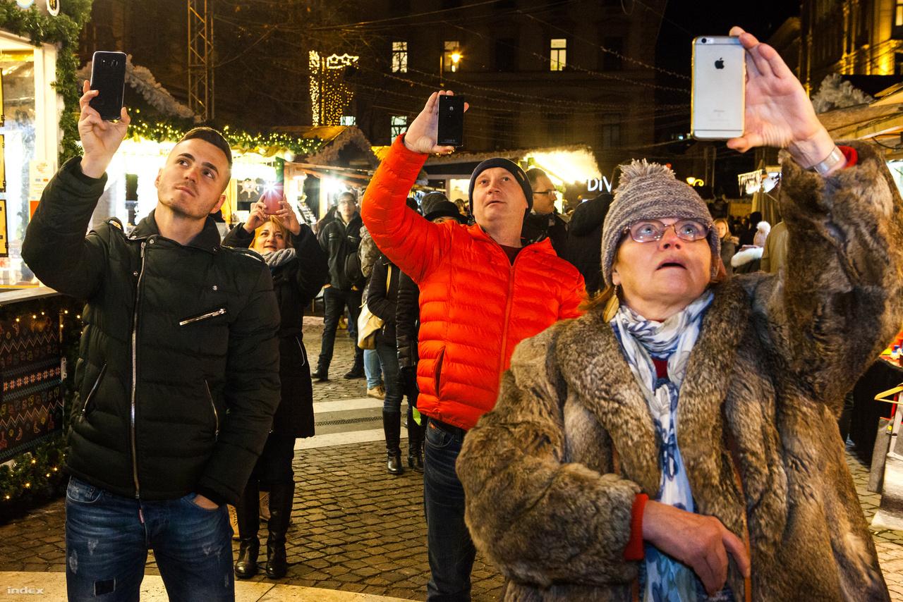 Fényfestést néző emberek a Szent István téri karácsonyi vásáron