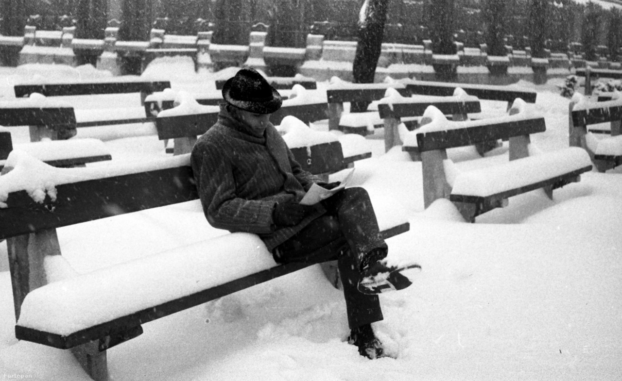 """Majd ha fagy.. címmel közölt cikket 1972-ben a Jövő mérnöke nevű műegyetemi lap, az írást a rettenetes hóviszonyok ihlették. """"Csodálatos időzítéssel majd' méteres hótakaró hullott az országra, így """"büszkén"""" állíthatjuk, hogy: az évszázad legkeményebb telét éljük át. E kétes """"büszkeségünkkel"""" sajnos rengeteg gond szakadt a. nyakunkba. Az országos problémákról napákig beszélgettünk, de az, egyetem se maradhatott ki az égi ajándékból, hiszen sokáig csak gyalogsági ásóval lehetett utat vágni a derékig érő hóban!                          Az egyetemi hóhelyzet szakértője Walkó László, az üzemeltetési és karbantartási osztály vezetője kicsit gondterhelten emlékszik vissza a nehéz időkre. A gyors reagálásiak köszönhetően (már a hó- ,szakadást, követő napon megalakították az egyetemi """"válságstábot""""). nagyobb fennakadás nélkül sikerült átvészelni a hideg támadását"""" - írja a cikk. A fotón a Műegyetem K épületének sarkánál található padoknál olvasgat valaki 1972 telén."""