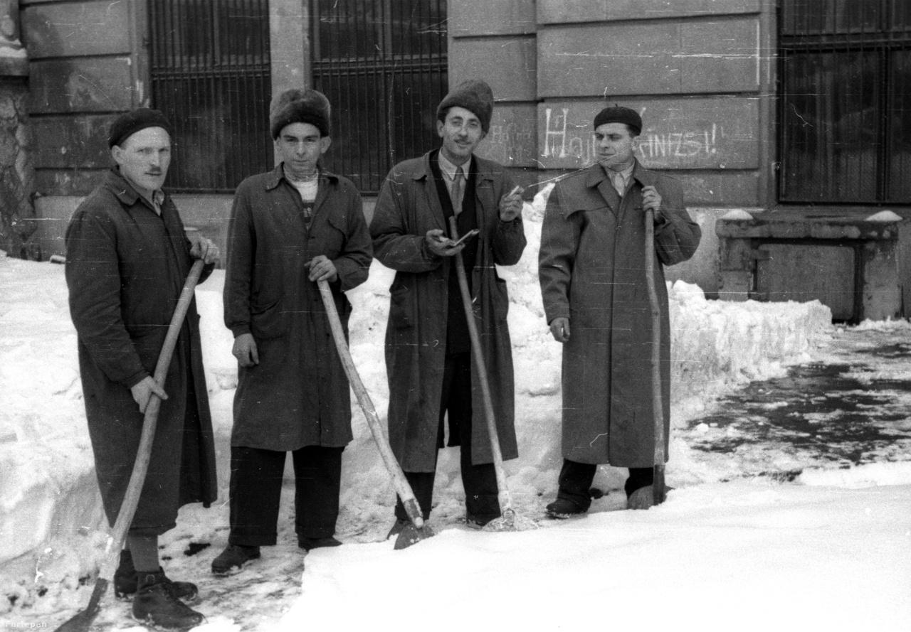 """Vigyáztak a hómunkások egészségére az ötvenes évektől, legalábbis a Magyar Közlöny 1952-es határozata szerint a Magyar Népköztársaság minisztertanácsának rendelete szerint az alkalmi hómunkásoknak is járt már biztosítás. """"Az államigazgatás szervei, az államhatalom helyi szervei, valamint üzemei, végül a magyar posta és a közforgalmú vasutak által alkalmazott alkalmi hómunkások üzemi baleset vagy foglalkozási betegség által öltözött munkaképességcsökkenés vagy megrokkanás esetében baleseti járadékra, illetőleg rokkantsági nyugdíjra jogosultak."""" A fotó 1951-ben a Corvin téren, a Budai Vigadó előtt készült."""