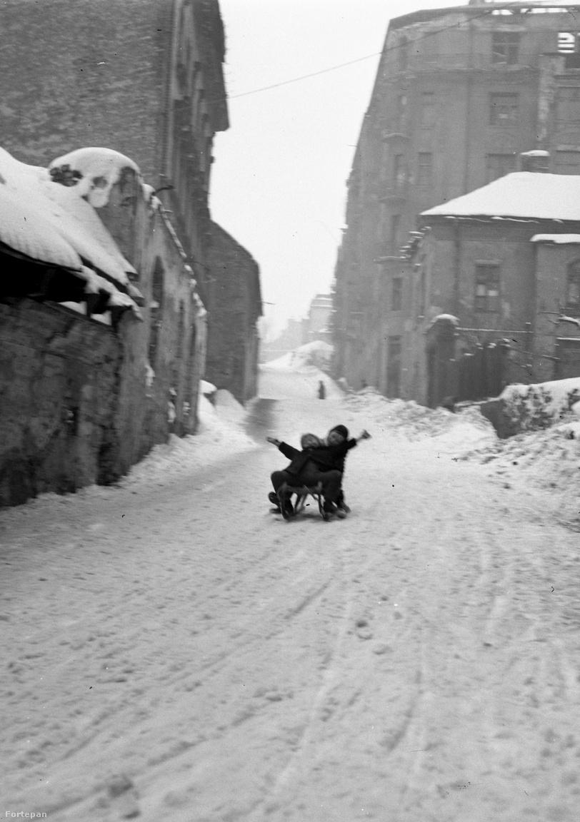 """Valószínűleg a Fiath János utca úttestén 1946-ban szánkózó gyerekek szabálysértést követnek el, ugyanis akkoriban nem lehetett Budapesten akárhol csúszkálni. """"Szánkázni és síelni a fővárosi tanács rendelkezése alapján csak a kijelölt helyeken szabad. A Gellért hegyen csak a déli lejtőn, a Ménesi-út és a Villányi-út közötti magánterületen szabad szánkózni, az Összes kocsival járható utón azonban tilos a szánkózás. Csak a gyermekek szánkózhatnak az Orbánhegyi-út, Istvánliegyi-út, Nárcisz-utca között, a Tündér-utcán és a Kissvábhegyi-uton azonban gyermekek és felnőttek egyaránt sportolhatnak. A Svábhegyen, az Istenhegyi- útón. a Mátyás király-útón, a Normafa-útón, a Márton hegy i-úton és a Diana-úton tilos a szánkózás. A Karthausi-úti portpályán csak """" - írta 1927-ben a 8 órai újság."""