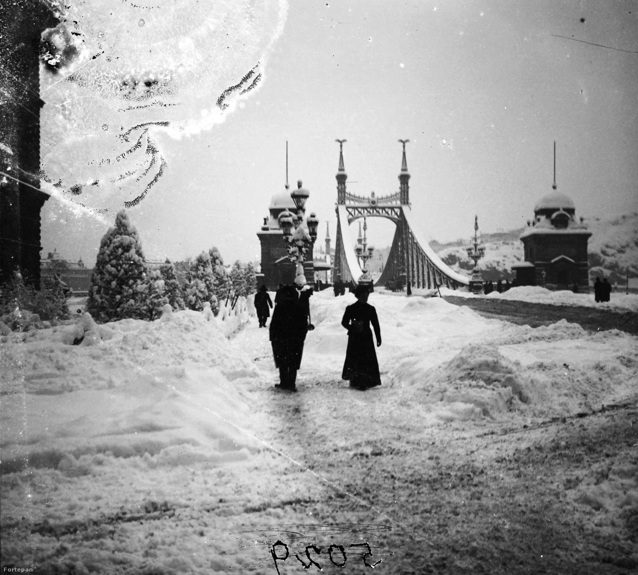"""1907 decemberében különösen erős havazás sokkolta az országot, hogy a tömegközlekedés megszűnt. """"A budapesti halandók csütörtökön reggel arra ébredtek, hogy nemcsak nagy havazás van, de a villamosok és az omnibuszok sem állanak rendelkezésükre, így aztán az óriási többség gyalogolni volt kénytelen, mert vajmi kevésnek adatott osztályrészül, hogy kétlovas kocsiba üljön és háromszoros taksát fizessen. Olyanok még akadtak volna, akik az egy- lovasokat vették volna igénybe, dehát a konflisok nyomtalanul eltűntek, mint a decemberi nagy havazások idején, amikor szintén nem mutatkoztak. Ezt különben okosan tették, mert az utcákat meg- fekvő hatalmas hótömegeken át ezer métert sem tudtak volna tenni. A kényelemhez szokott budapestiek tehát az apostolok lovait vették igénybe s az egy órai utat két óra alatt tették meg, mert minden két- lépés után egyet visszacsúsztak"""" - írta a Pesti Hírlap 1907 februárjában. A Fővám tér, a Szabadság (Ferenc József) híd pesti hídfője, balra a Fővámpalota látható 1907-ből a képen."""