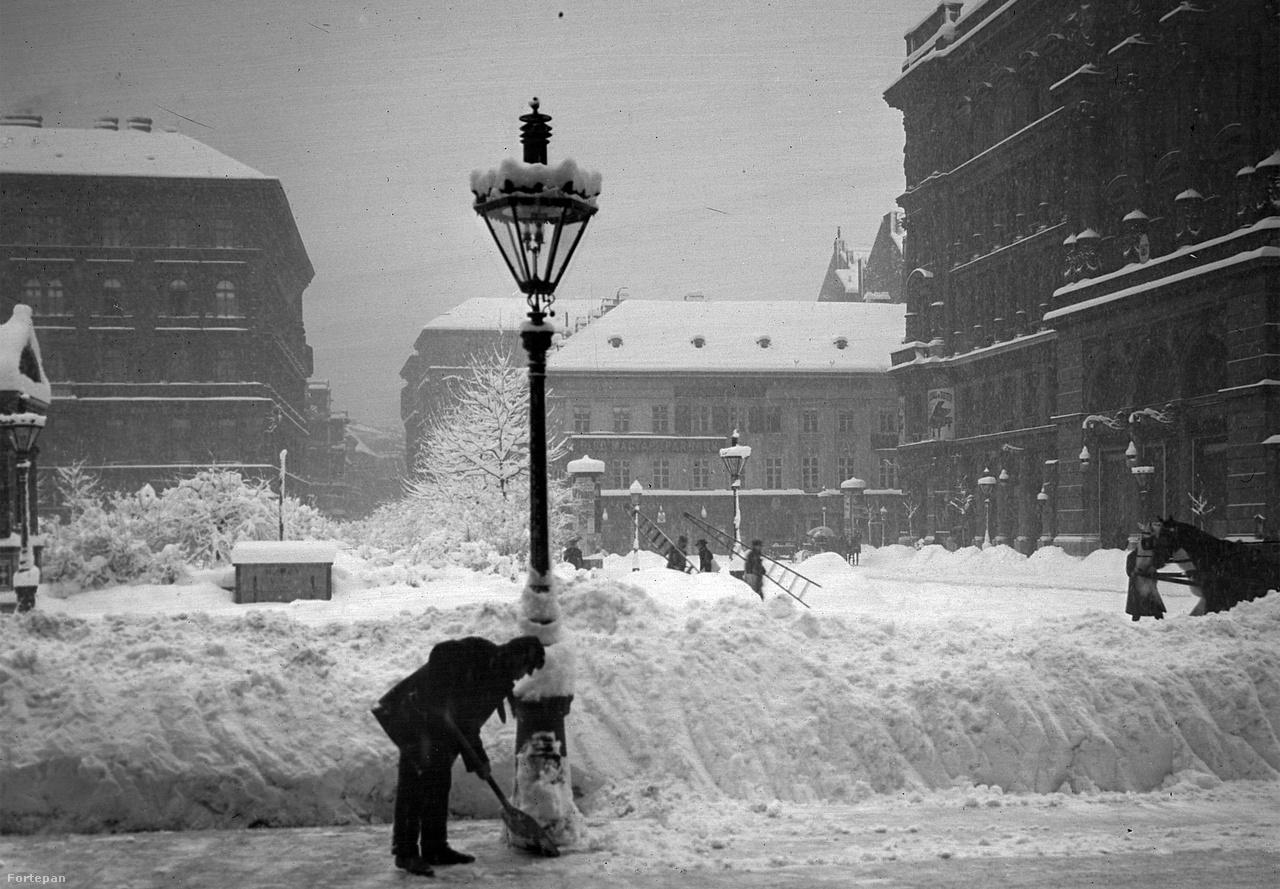 """Még mindig 1907-ben járunk, a Vörösmarty téren szorgos hómunkás dolgozik, szemben a Váci utca torkolata látható. """"Az óriási mennyiségű hó eltakarítása nagy gondot okoz a főváros köztisztasági hivatalának. Szerda estétől kezdve 2100 rendkívüli és 806 állandó munkás dolgozik a hó eltakarításán. A köztisztasági hivatal újabban ismét 120,000 koronát kért a költségekre. A hó eltakarítása következtében igen sok munkás gyűlt össze, hogy felajánlják magukat. A munkásokat azonban bujtogatók felizgatták, hogy ne dolgozzanak a rendes napibérért, hanem követeljenek nagyobb fizetést, mert a villamos társaságoknak és a fővárosnak szüksége van reájük.                          A bujtogatók elérték céljukat, amennyiben a munkásak között csakhamar elégedetlenség támadt"""" - írja a Pesti Hírlap újságírója 1907 februárjában."""