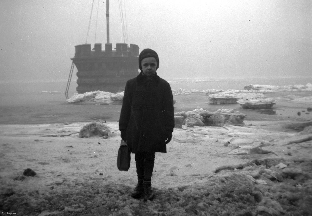 """Áradt a Duna a Lánchíd közelében 1940-ben, és talán éppen a fotón a Lánchíd közelében álldogáló gyerek mögött nyugodott a víz mélyén Kató, a nagy médiafigyelmet befutó kotrógép. Pár hónappal a zord tél után, májusban emelték ki egy csomó bámészkodó előtt Katót, a kotrógépet a vízből, ami még a jégzajlások idején csúszott a folyóba. """"A Ganz-hajógyár óriási emelődaruja sáros, rozsdás alkotmányt emelt a magasba. Nemsokára tisztán kibontakozott                          a vastag drótköteleken és emelő                         láncon magasba vont kotrógép, a """"Kató"""" körvonala. A kotrógép még a tavaszi jégzajlás idején szabadult el Vácról és jégtáblák sodra egész a Lánchídig sodorta, A budai hídfőnél azután megakadt egy gödörben és elmerült. Leszállt a vízbe a Ganzhajógyár búvára, Szulyovszky Rezső, aki a 11 méter mélységben a nyolctonnás kotrógépet                          megláncolta, horgot akasztott rá,                          A kiemelés munkálatai reggel óta, tartottak. Egy ízben a daru csigájáról lecsúszott a drótkötél és emiatt késett a kotrógép kiemelése.                          Az esti órákban már el is vontatták a """"Kató""""-t, munkások kiásták belőle a sarat, megtisztították és amint hírlik, árverés alá kerül a váci partokhoz hűtlen kotrógép"""" - számolt be 1940 májusában a Népszava."""