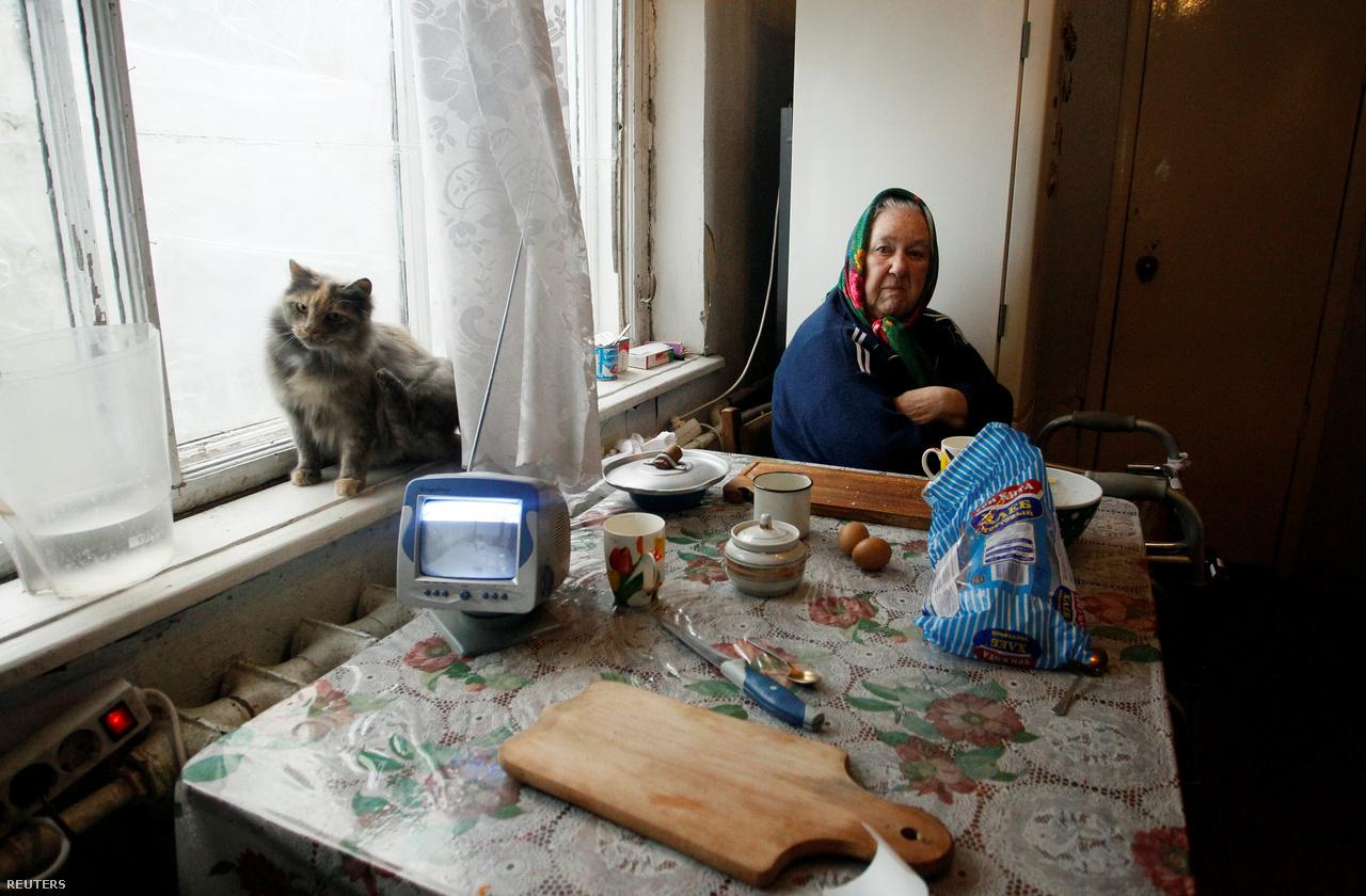 Idős asszony Donyeck nyugati szélén, az Október kerületben. Ez a térség Piszki elővárossal és közelben lévő, lényegében megsemmisült nemzetközi repülőtérrel együtt súlyos harcok helyszíne volt 2014-2015-ben. Akinek volt hová mennie, elhagyta a városrészt, de volt, aki inkább megpróbált alkalmazkodni a háború utáni körülményekhez. Donyeck megye oroszbarát szakadárok ellenőrizte területén 2,3 millió ember él, 29 százalékuk nyugdíjas. A nyugdíjak 2 300 rubeltől, körülbelül 10 ezer forinttól indulnak, de a dupláját már kevesen kapják. A jó fizetések 10 ezer rubel körül vannak. Az orvosoknak be kell érniük 4-9 ezer rubellel. A legjobban a hivatásos katonák keresnek 15 ezer rubellel és a tisztek, akik akár 35 ezer rubelt is kaphatnak, ez kb. 140 ezer forint.