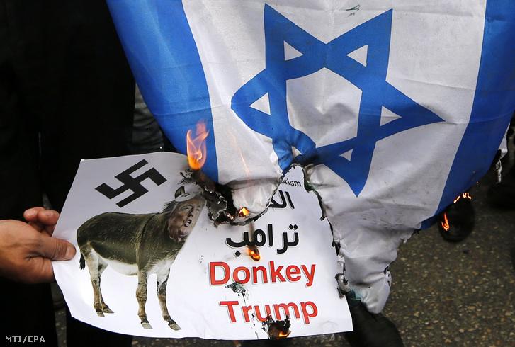 Palesztin tüntetők izraeli zászlót égetnek a Donald Trump amerikai elnök Jeruzsálem státuszáról tett bejelentése elleni tiltakozáson a ciszjordániai Hebronban 2017. december 20-án.
